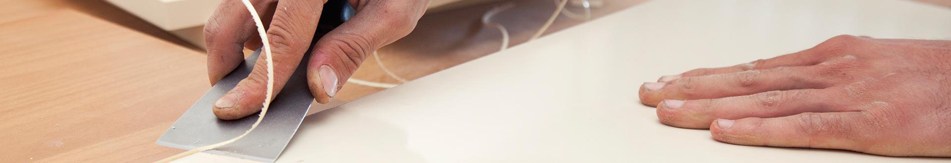 Pracownik odcinający nadmiar okleiny